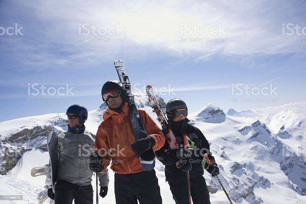 Skiers and a snowboarder on a mountain carrying their equipment royalty-free stock photo