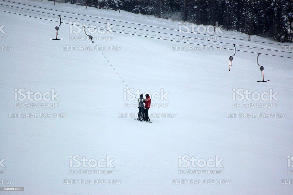 Skiers and ski lifts on ski area stock photo