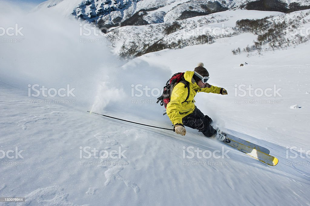 Skiers and snow flying stock photo