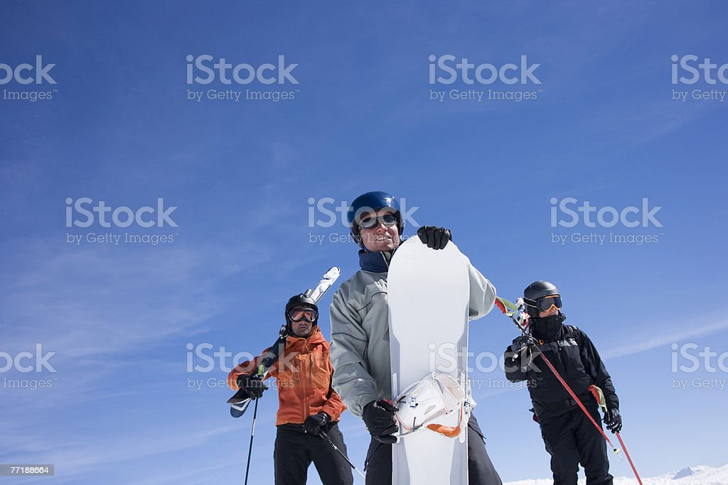 Skiers and snowboarder standing on mountain royalty-free stock photo
