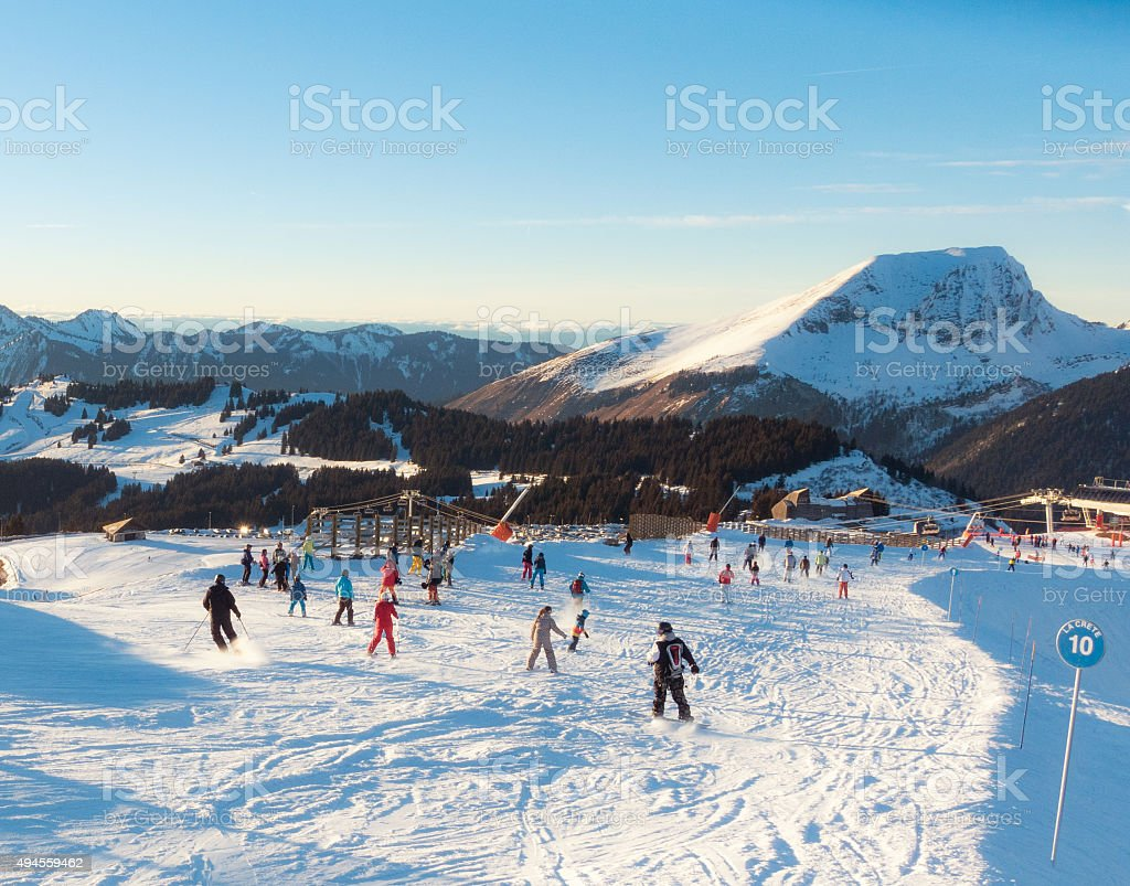 Skiers and Snowboarders on a blue piste in the Alps stock photo