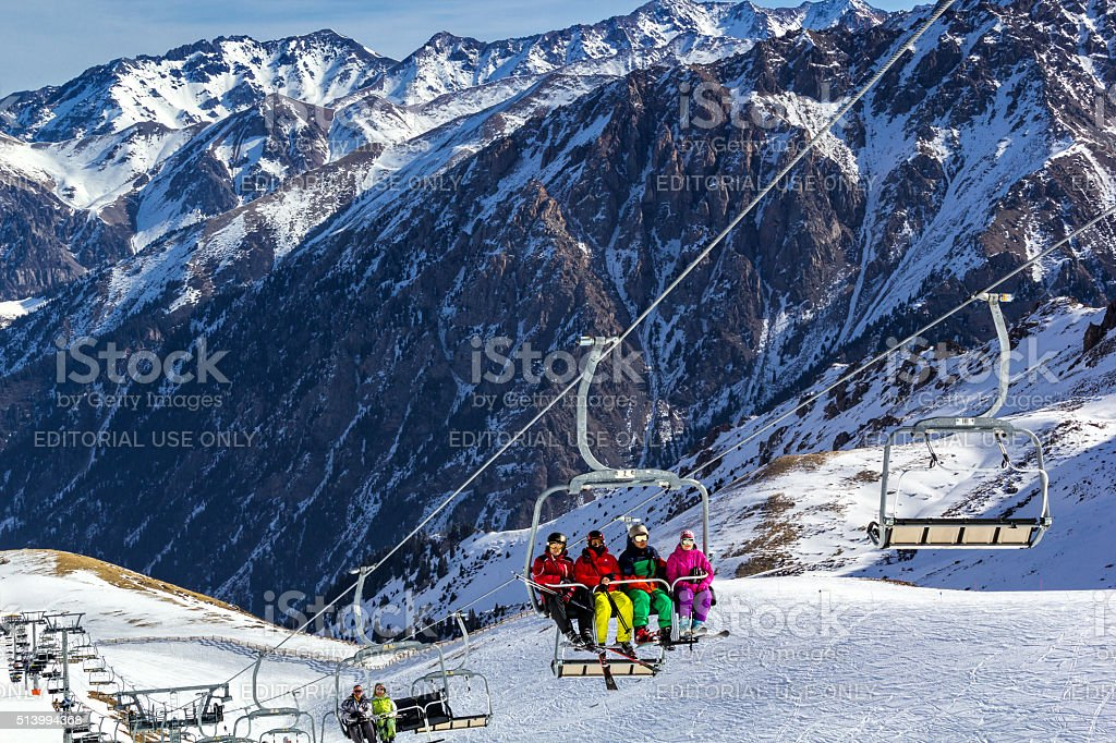Skiers ascend the mountain on a lift stock photo