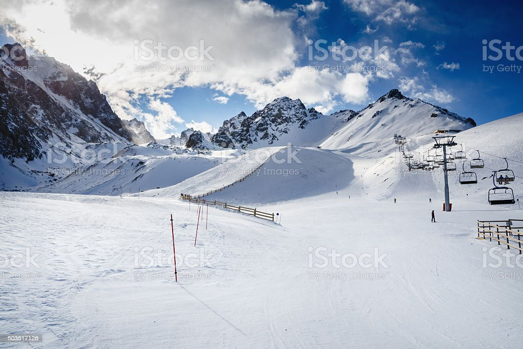 Skiers going down the slope under ski lift. stock photo