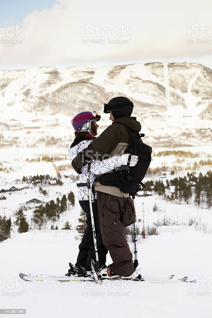 Skiers hugging on mountain top stock photo