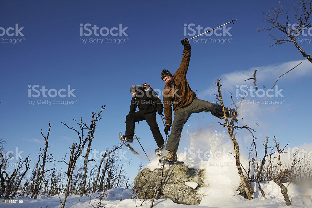 Skiers jumping off rock in snow stock photo