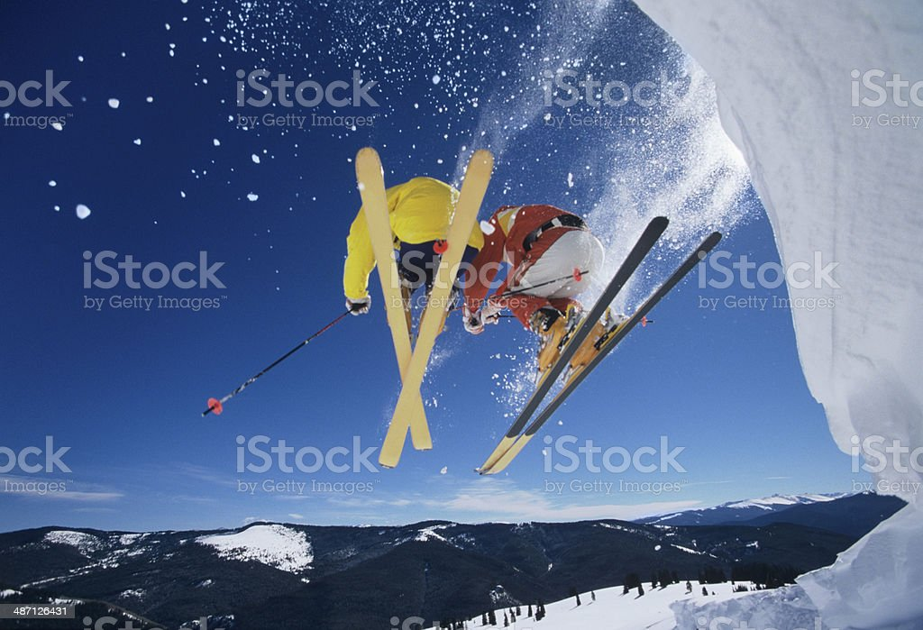 Skiers Launching Off Snow Bank Hitting The Slopes stock photo