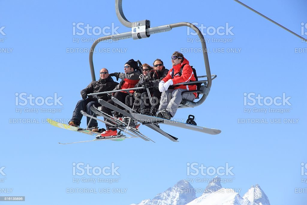Skiers on a chairlift stock photo