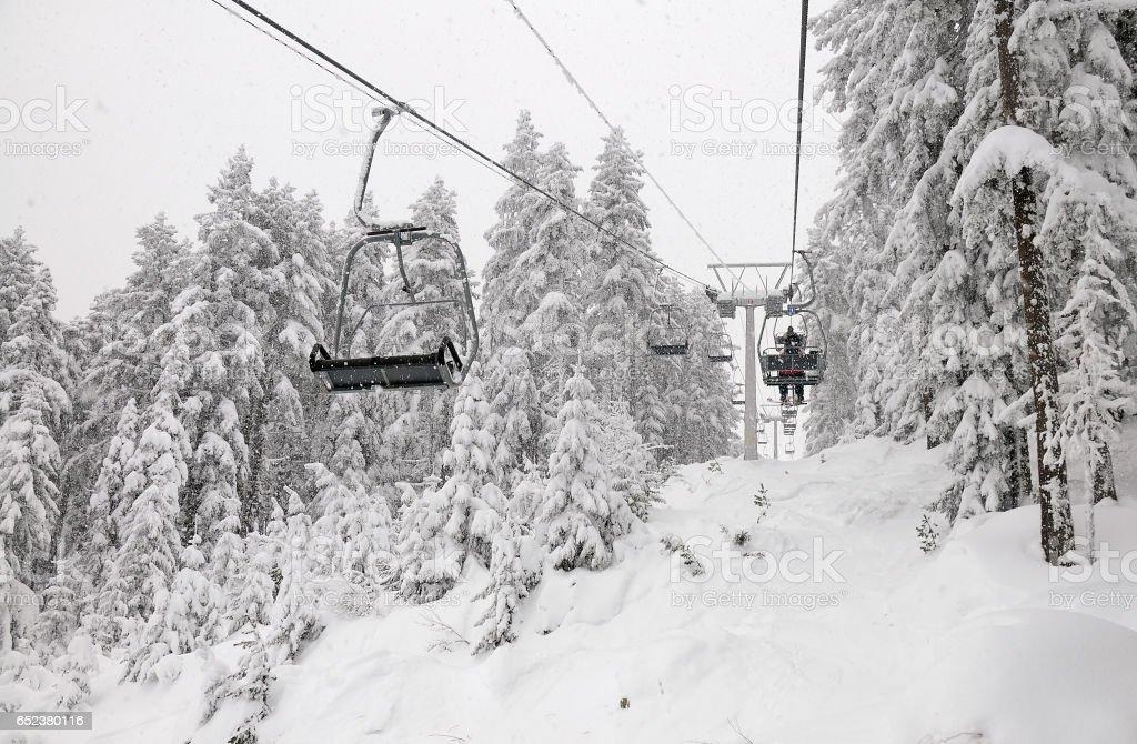 Skiers on a ski-lift in Rila Mountain resort Rilski ezera stock photo
