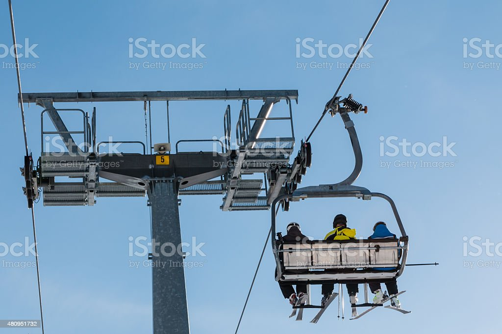 Skiers on chairlift in mountain stock photo