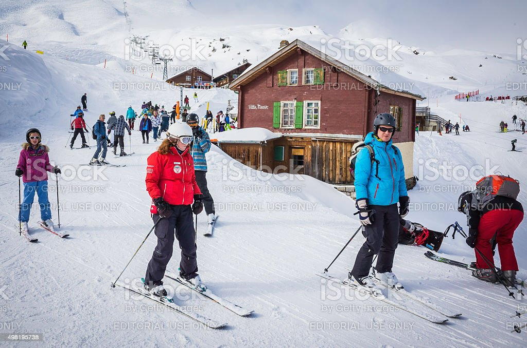 Skiers on groomed slopes crowded winter ski resort Alps Switzerland stock photo
