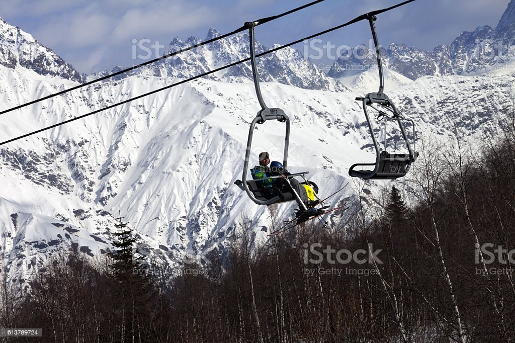 Skiers on ski-lift and snow mountains at winter sun day stock photo