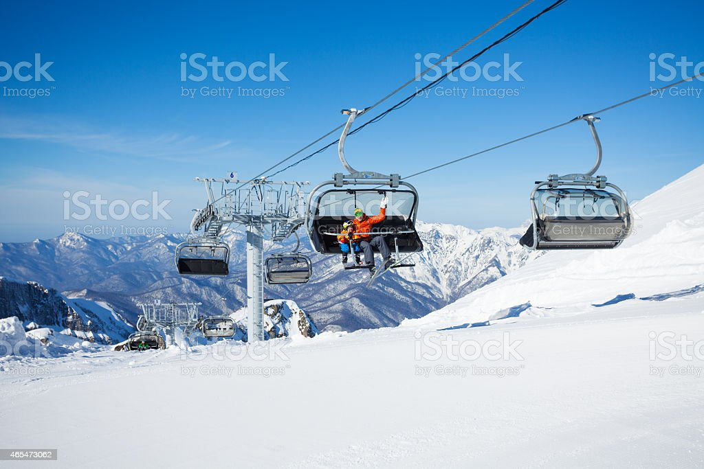 Skiers on the chairlift ropeway winter resort stock photo