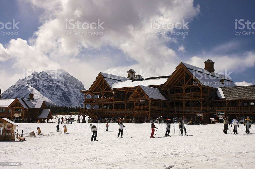 Skiers resting in front of a brown ski chalet royalty-free stock photo