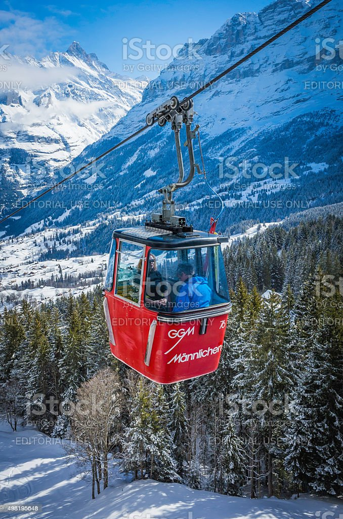 Skiers riding cable car above snowy Alpine mountain forests Switzerland stock photo