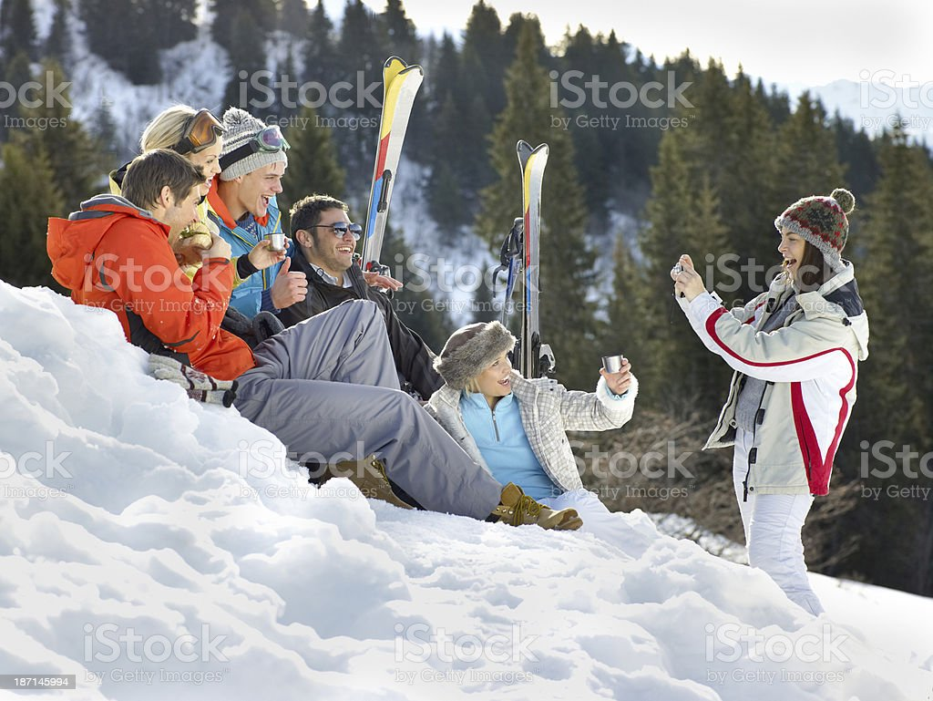 Skiers Sitting In Snow Posing For A Photo stock photo