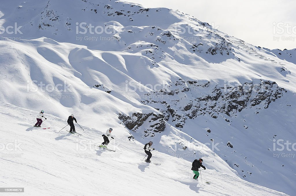 Skiers skiing together on slope stock photo