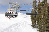 Skiiers and Snowboarders Riding Up a Ski Lift