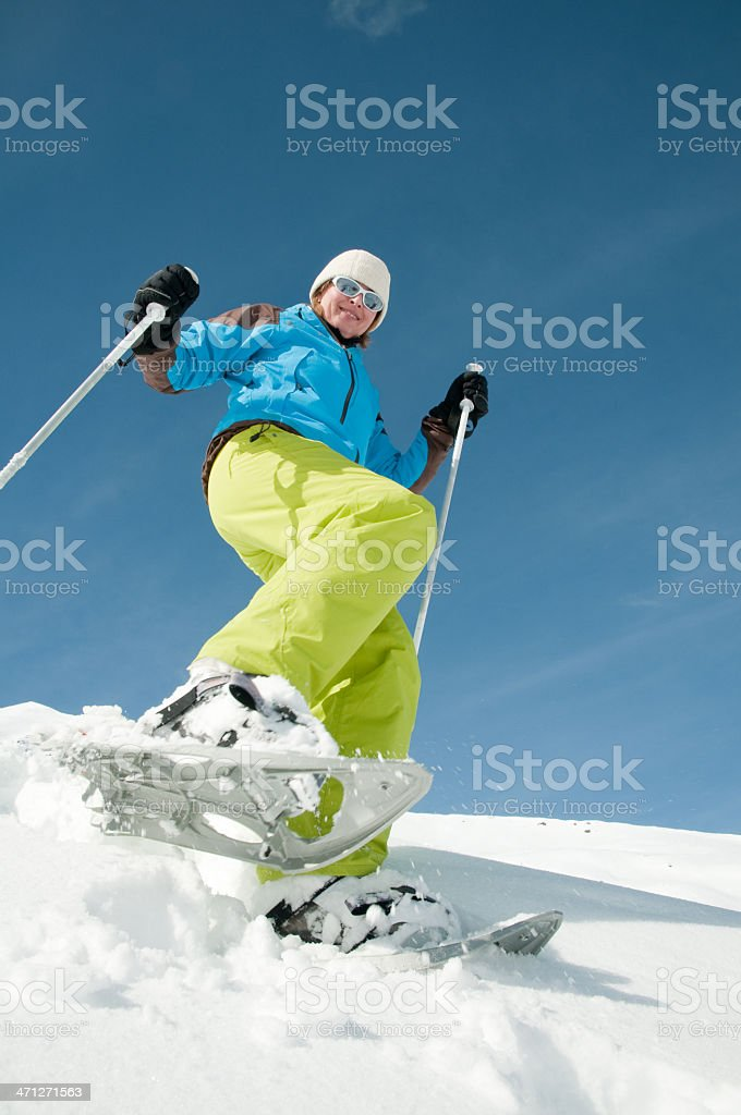 Skiing in the snow wearing a blue jacket royalty-free stock photo