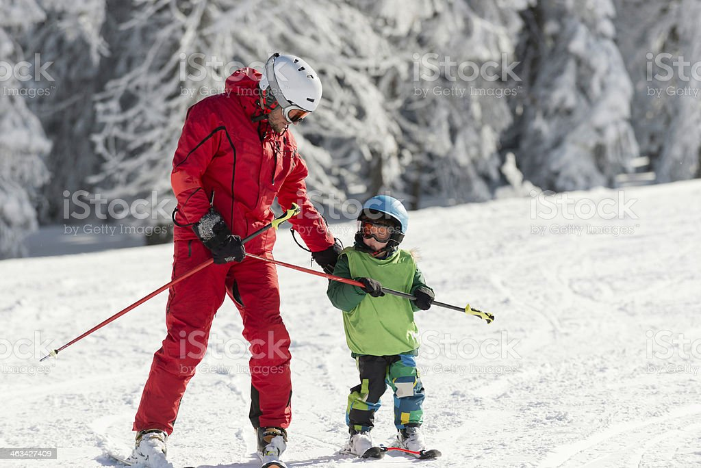 Skiing instructor with little boy stock photo