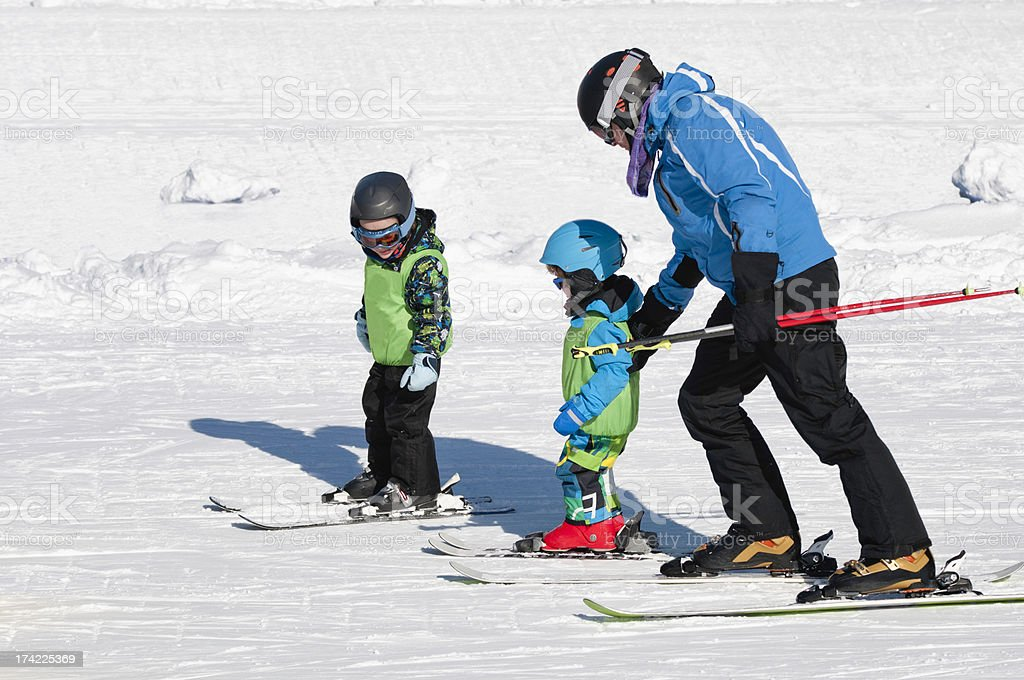 Skiing instructor with two little boys stock photo
