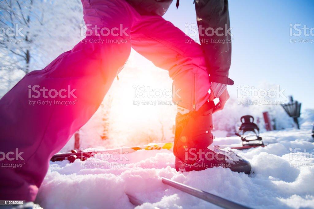 Woman adjusting ski boots