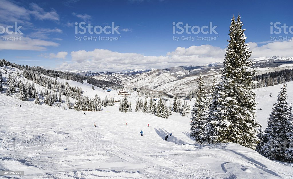 Skiing Slopes with Rocky Mountains in Background stock photo