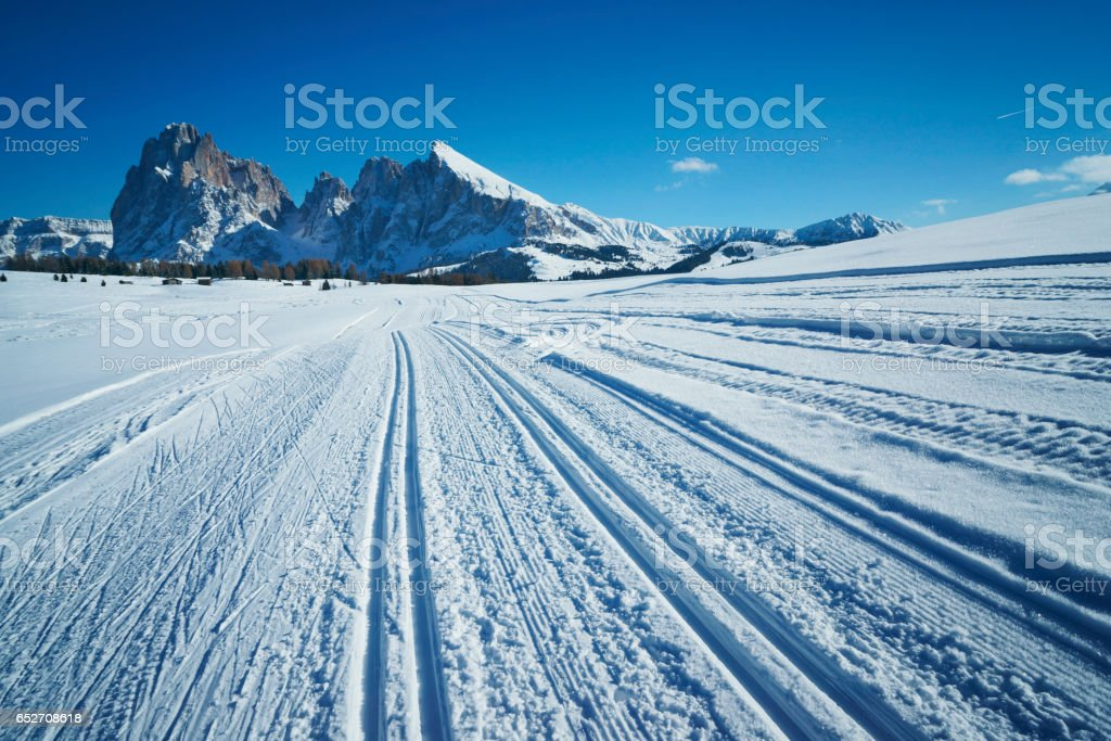 skiing tracks in snow covered Dolomite alps landscape with mountains stock photo