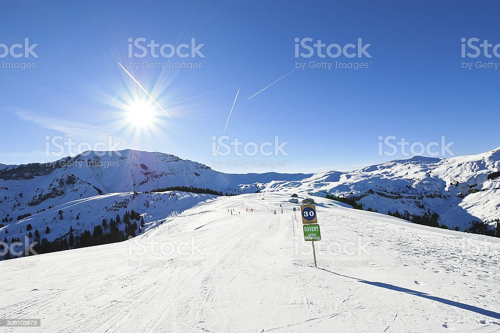 skiing tracks on snow slopes in sunny day stock photo