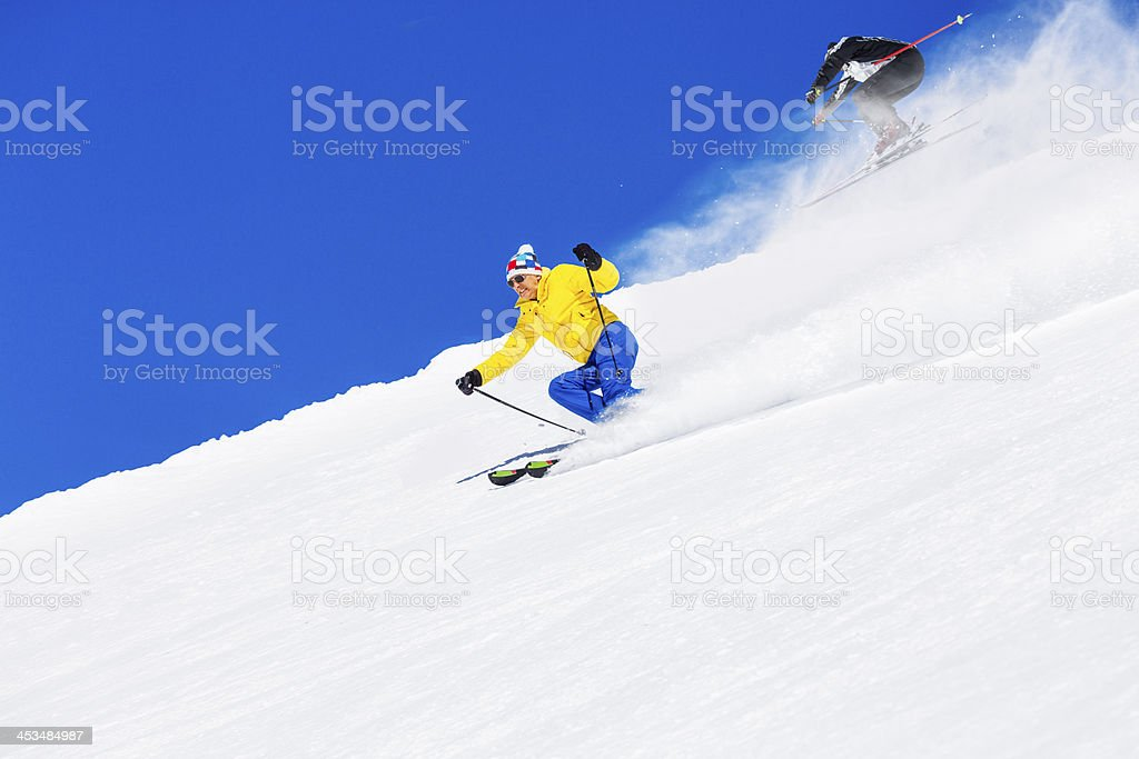 Snow skiers, skiing carving at high speed, mountain ski resort in the...