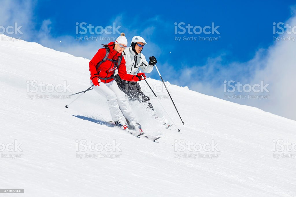 Couple. Snow skiers, skiing carving at high speed, mountain ski...