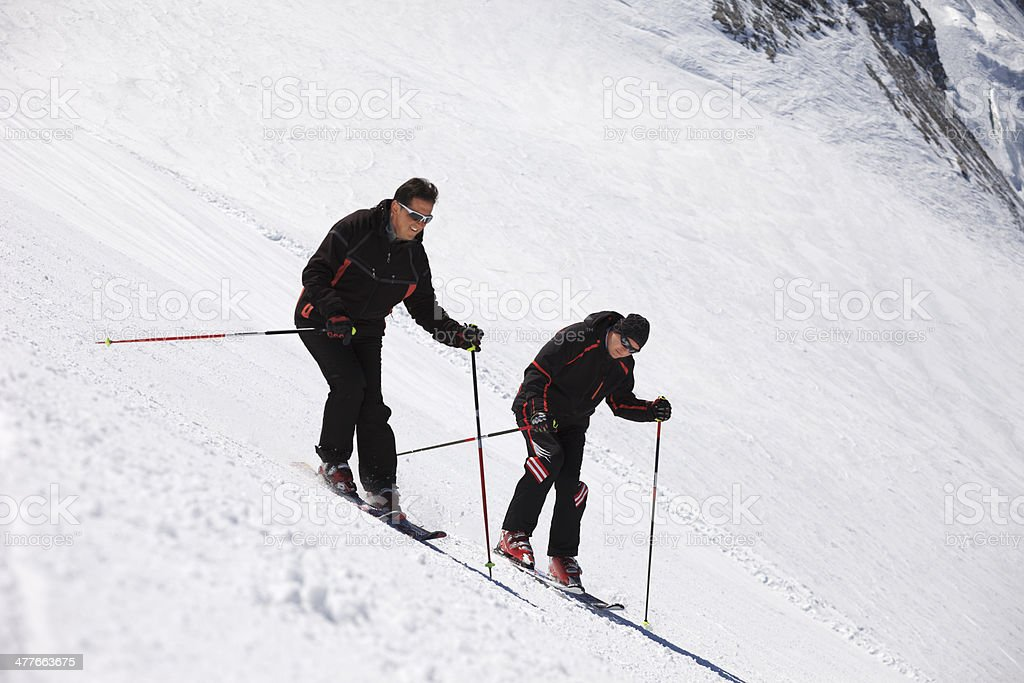 Best Friends. Snow skiers, skiing carving at high speed, mountain ski...