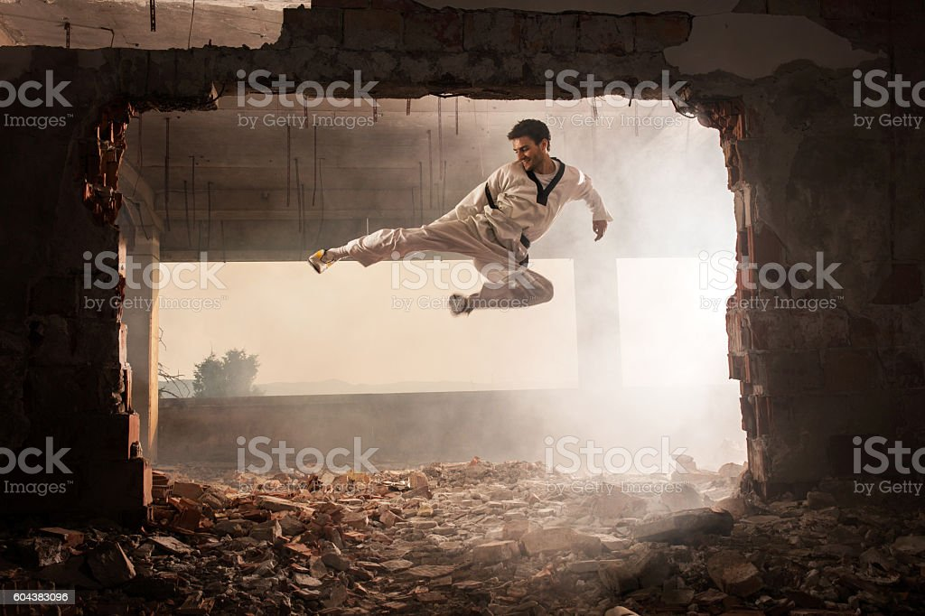 Skilful martial artist performing jump kick among ruins. stock photo