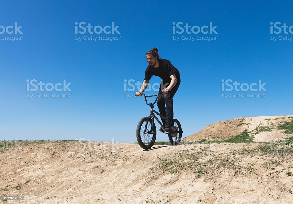 Skilful young extreme cyclist on bike in nature. stock photo