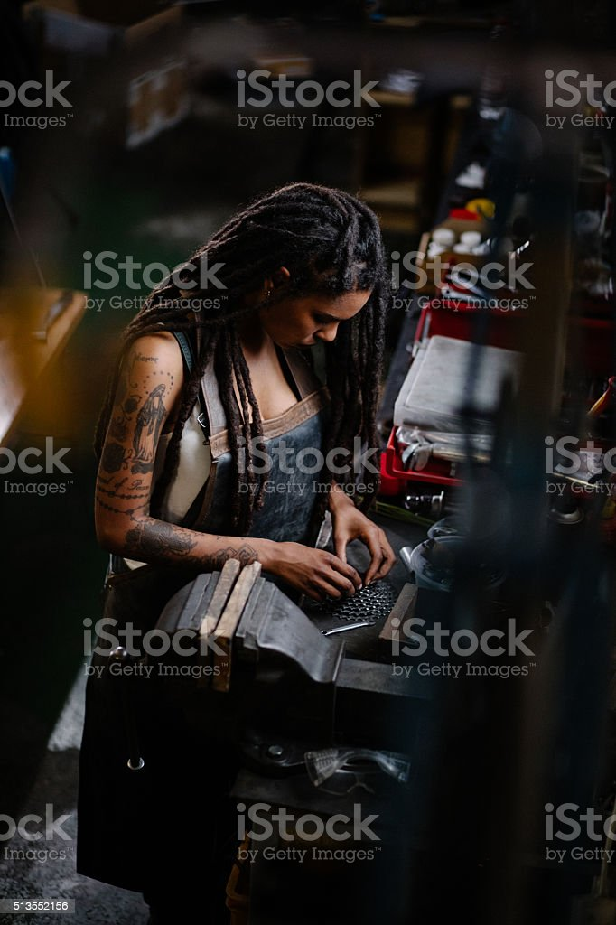 Skilled female bicycle mechanic assembling gears in her workshop stock photo