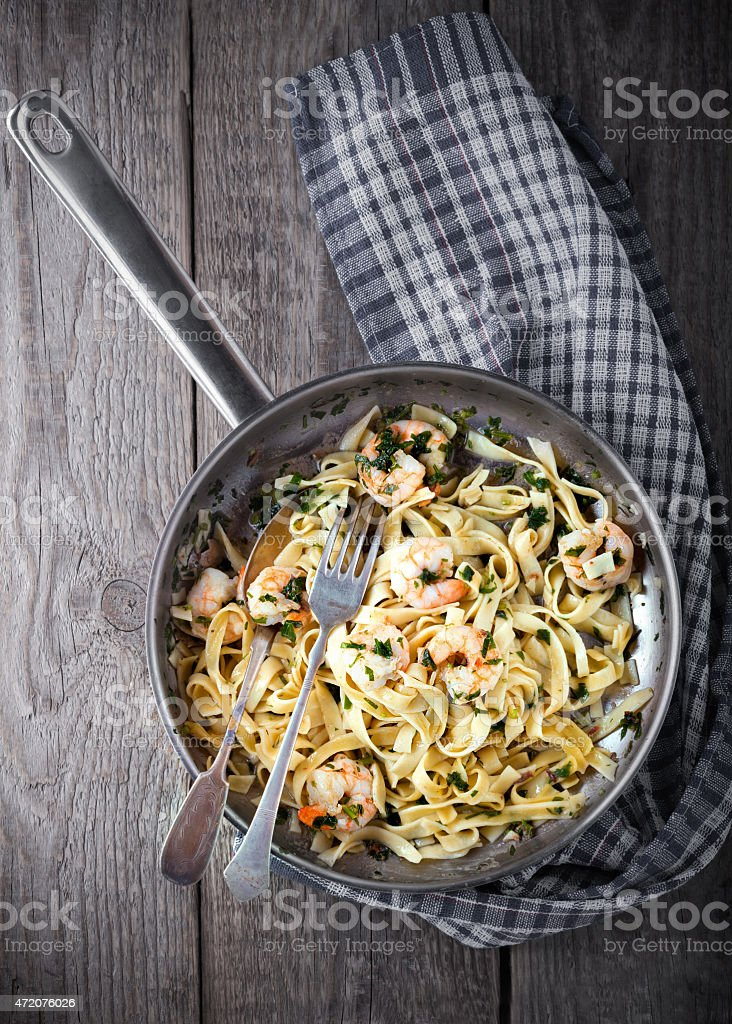 A skillet of pasta with shrimp on a checkered cloth stock photo