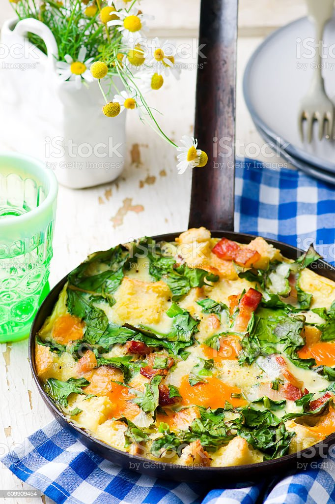 Skillet Strata with Bacon, Cheddar, and Greens stock photo