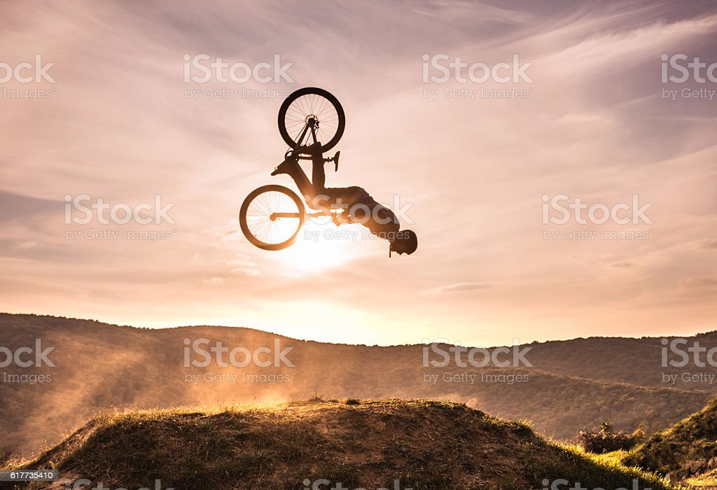 Skillful cyclist doing backflip against the sky at sunset. stock photo