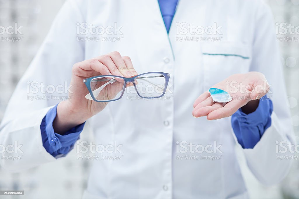 Skillful female optician is showing new glasses stock photo