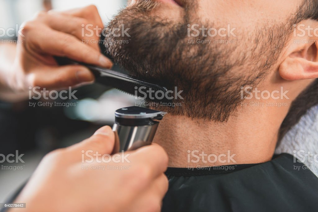 Skillful hairdresser shaving face of client stock photo