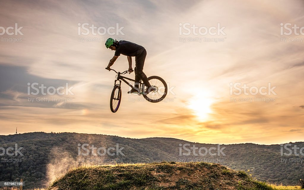 Skillful man on mountain bike practicing 360 xup at sunset. stock photo