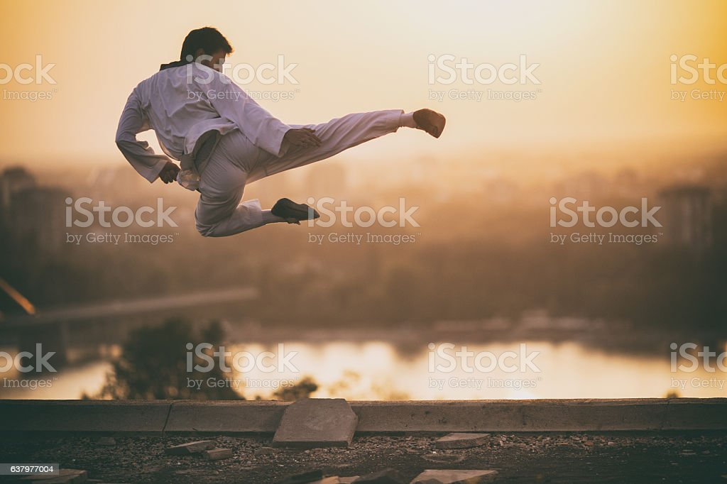 Skillful martial artist performing fly kick at sunset. stock photo