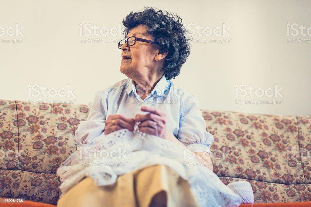Skillful senior woman making crochet stock photo