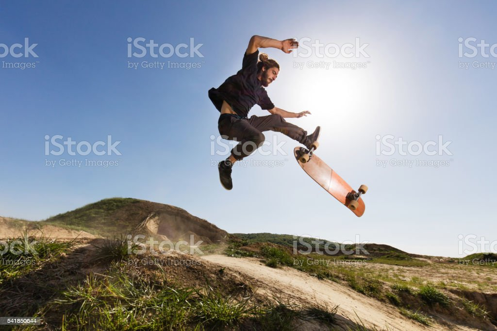 Skillful skateboarder practicing Ollie against the blue sky. stock photo