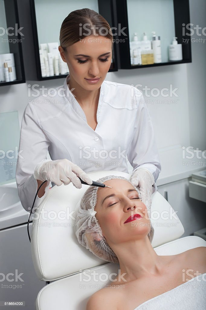 Skillful young cosmetologist is serving her patient stock photo