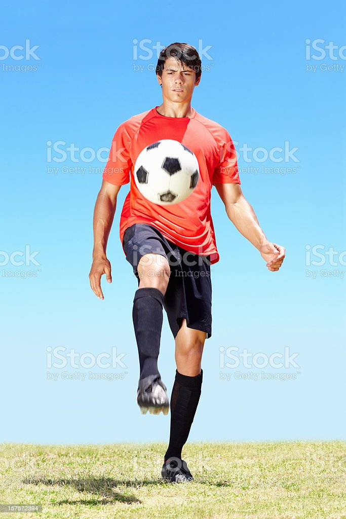 Skillful young footballer practicing at the field royalty-free stock photo