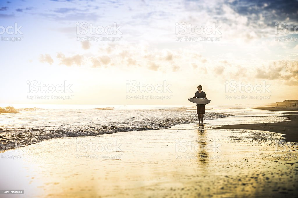 Skim boarder at sunset on a beach stock photo
