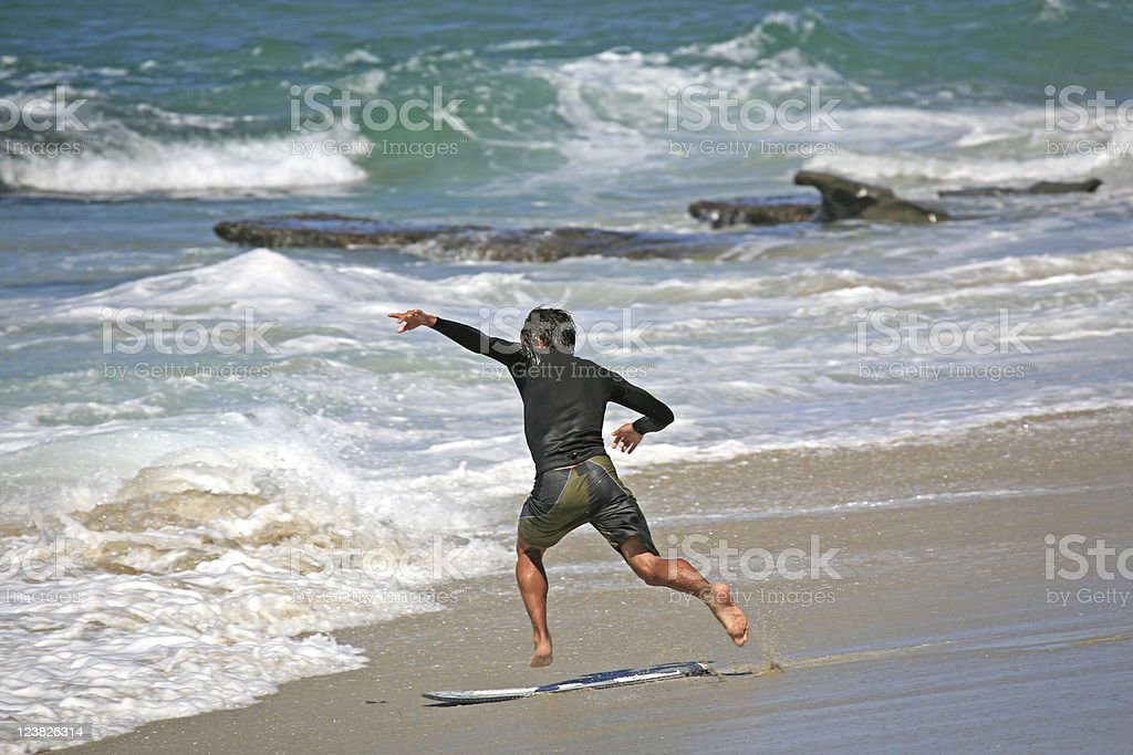 Skim boarder jumping on-board stock photo