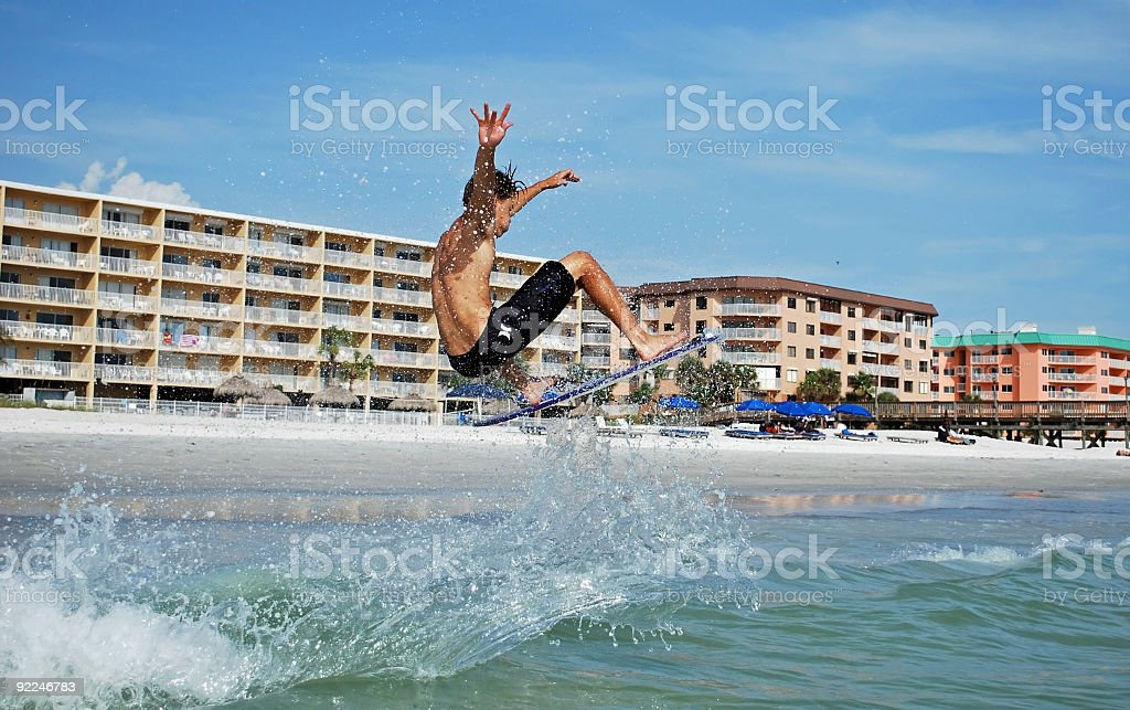 Skimboarder Catches Air with Trailing Sea Spray stock photo