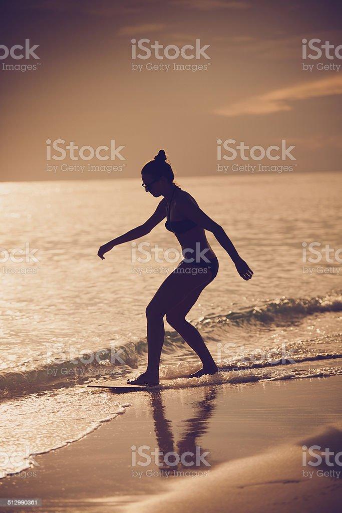 skimboarding at sunset stock photo