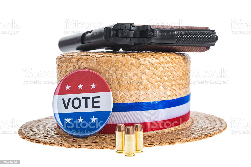 Skimmer hat with VOTE button, gun and bullets on white stock photo